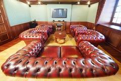 有皮革扶手椅子的英国雪茄室休息的 库存照片