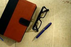 有皮革盖子、笔和镜片的笔记本 免版税库存照片