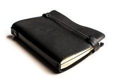 有皮革盖子的黑笔记本在透视 库存照片