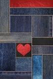 有皮革纹理的牛仔布牛仔裤和心脏形状背景,补缀品与皮革样式的牛仔布斜纹布 图库摄影