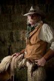 有皮革背心、牛仔帽和围巾画象的地道西部牛仔 库存图片