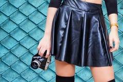 有皮革裙子和葡萄酒照相机的女孩 库存照片