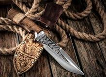 有皮革鞘的猎刀在一张木桌上 免版税库存照片