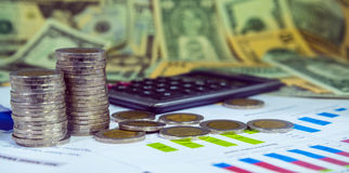 有益于在财政报告的图与硬币和计算器 免版税图库摄影
