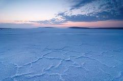 有盐水晶的盐湖沙漠在前景的在日落 库存图片