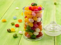 有盒盖的玻璃瓶子用在木绿色背景的五颜六色的糖果填装了 库存图片