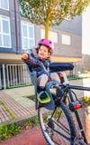 有盔甲的小女孩在坐在自行车的头 免版税图库摄影