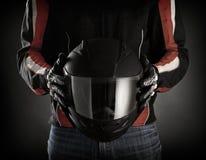 有盔甲的摩托车骑士在他的手上。黑暗的背景 免版税库存照片