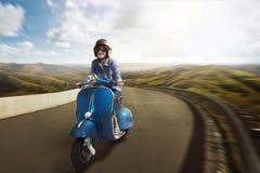 有盔甲的年轻亚洲妇女骑马小型摩托车 免版税库存照片