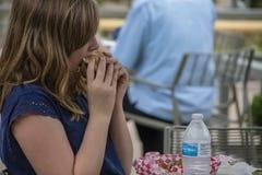 有盖她的面孔的头发的女孩咬一口一个大汉堡包在与被装瓶的水和法语的室外桌上 免版税库存图片