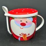 有盖子和匙子的快活的圣诞老人陶瓷杯子 库存照片