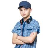 有盖帽和耳机的青少年的男孩 免版税库存图片