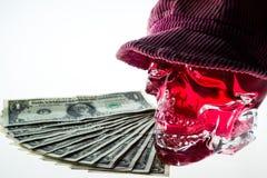 有盖帽和金钱的红色头骨 免版税库存图片