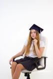 有盖帽毕业生的女小学生坐椅子,考虑未来 图库摄影