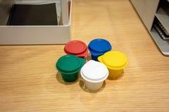 有盖帽的五颜六色的微型塑料杯子在木桌上 库存照片