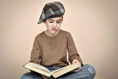有盖帽的年轻男孩读一本旧书的 免版税库存图片
