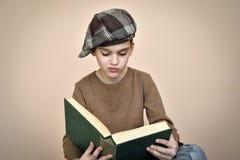 有盖帽的年轻男孩读一本旧书的 库存图片