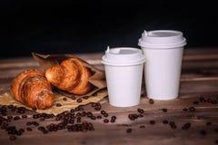有盖帽的白皮书杯子在前面提出了 咖啡杯和咖啡豆,新月形面包,在棕色木桌上 库存图片