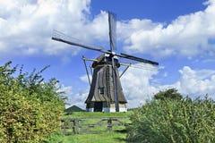 有盖的屋顶的排水设备风车在有剧烈的形状的云彩和蓝天的,荷兰一个开拓地 免版税图库摄影