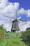 有盖的屋顶的排水设备风车在有剧烈的形状的云彩和蓝天的,荷兰一个开拓地 免版税库存照片