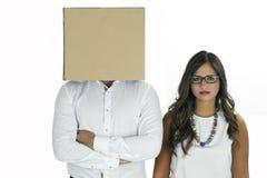 有盖他的头和妇女的纸板箱的一个人 免版税库存照片