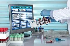 有盘子血样的医生在计算机前面的手上  免版税库存图片