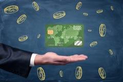 有盘旋在它上的一张绿色普通信用卡的一棵开放商人` s棕榈在黑板背景 库存图片