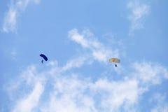 有盘旋在landin的队列的五颜六色的滑道的两个跳伞运动员 库存照片