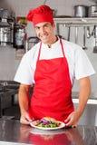 有盘的愉快的男性厨师 免版税库存照片