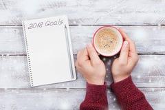 有目标在2018年和男性手的笔记本有咖啡的 计划和刺激的新年概念 顶视图 免版税库存图片
