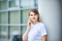 有直发的欧洲女孩谈话在电话 免版税库存照片