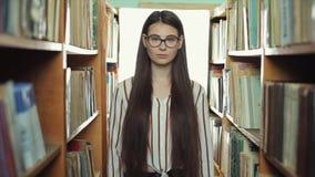 有直接长的黑色头发神色的美女到照相机里和步行在图书馆里beetween架子 股票录像