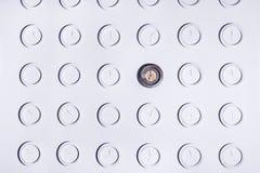 有相同圆的白色不数字时钟和一个独特的黑暗的时钟的白色墙壁 时间概念背景 库存图片
