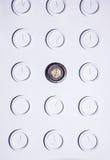 有相同圆的白色不数字时钟和一个独特的黑暗的时钟的白色墙壁 时间概念背景 免版税图库摄影