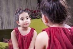 有相当红色摆在和看她自己的礼服和嘴唇的小美丽的阿拉伯中东女孩在镜子 8-10年 免版税库存照片