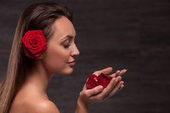 有相当红色花的可爱的亭亭玉立的女孩 库存图片