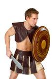 有盾的年轻男性战士 库存图片
