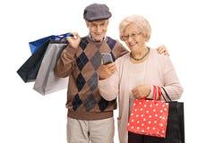 有看一个手机的购物袋的前辈 免版税库存照片