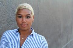 有看与一个轻松的中立表示的短的被染的金发的美丽的年轻非裔美国人的妇女照相机 免版税图库摄影