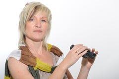有看与双筒望远镜的围巾的白肤金发的女实业家 免版税库存图片