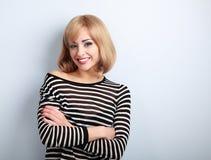 有看与的被交叉的双臂的美丽的愉快的偶然白肤金发的妇女 免版税图库摄影
