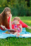 有看书的小女儿的妈咪坐毯子 免版税图库摄影
