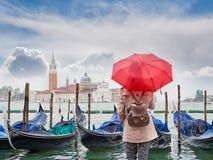 有看圣乔治Maggiore教会,威尼斯的一把红色伞的妇女 库存图片