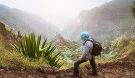 有看在与山峰的农村风景的背包的在尘土的旅客和山沟在从Xo的道路宣扬 免版税图库摄影