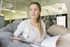 有看在办公室的片剂个人计算机和书的年轻女实业家 免版税库存图片