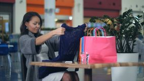 有看在咖啡馆的购物袋的亚裔少妇新的衣裳sittinf 库存照片