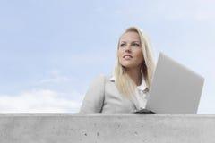 有看在大阳台的膝上型计算机的年轻女实业家反对天空 库存图片