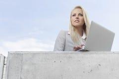 有看在大阳台的膝上型计算机的年轻女实业家反对天空 图库摄影