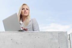 有看在大阳台的膝上型计算机的年轻女实业家反对天空 免版税库存图片