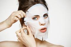 有看在白色背景的面部面具的女孩照相机 装饰性的程序 秀丽温泉和整容术 库存照片